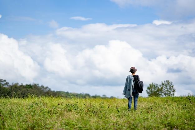 空の青と白の雲の丘の自然に立っている女性