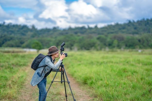女性カメラマンは丘の自然で写真を撮る、彼女はカメラを押しながら見ています。