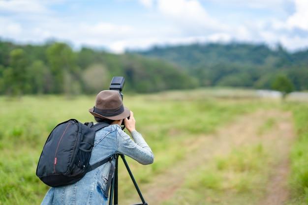 女性カメラマンが丘で写真を撮る、彼女はカメラを押しながら見ています。