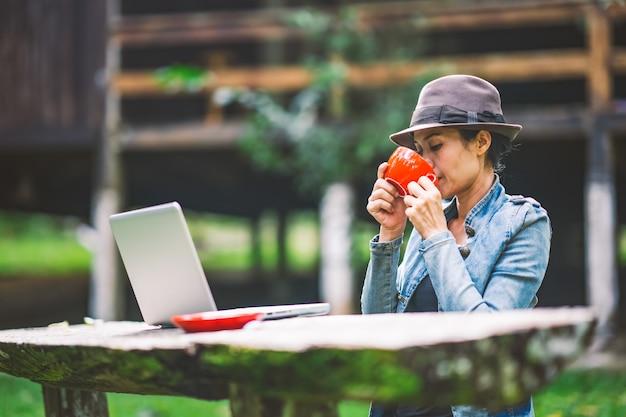 働く女性と休暇の休日のテーブルの上のコーヒーを飲む自然の丘の自然
