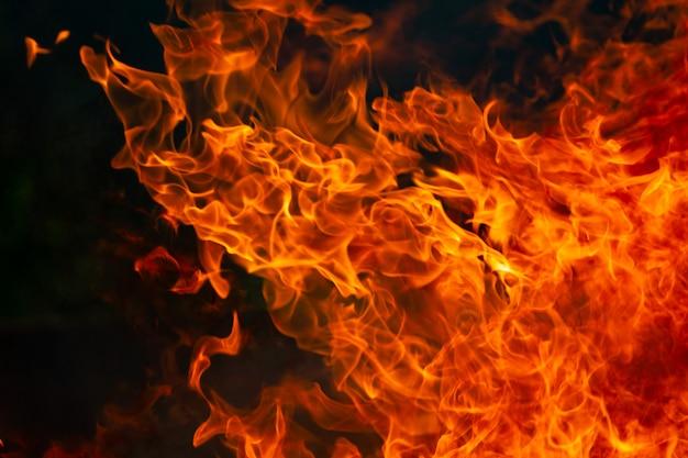 Горячий огонь пламя и дым горит на темноте