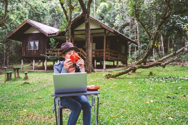 Женщина пьет кофе на холмах и прекрасную природу утром, девушка улыбается и рада работать на ноутбуке для онлайн-бизнеса в расслабленное время отпуск летом