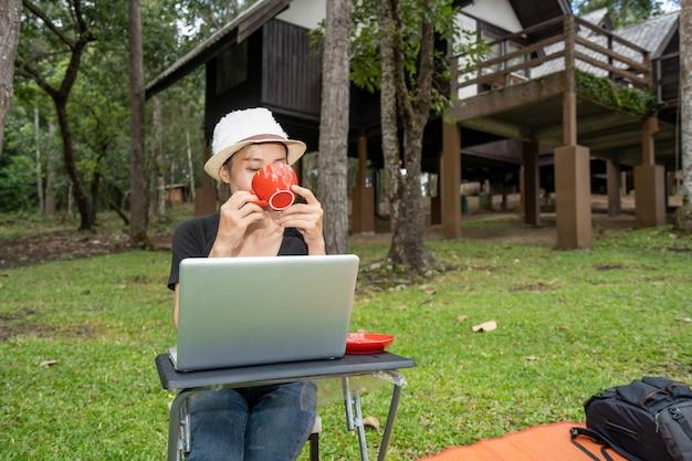 丘の自然に休暇の休日の時間にテーブルでコーヒーを飲む女の子