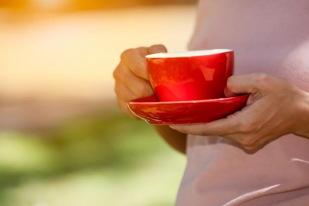 ぼやけた緑の朝に手で保持している赤いカップコーヒーセット