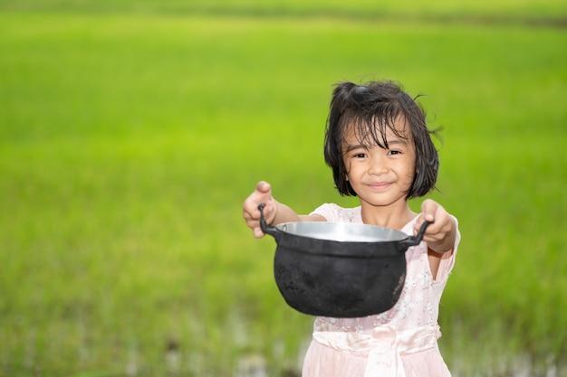 朝はぼやけ緑の田んぼにフードポットを保持している子供