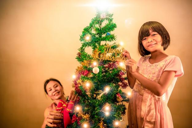 子供とお祭りシーズンのクリスマスツリーに座っている夜の母