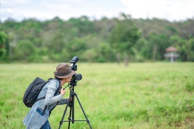 女性カメラマンが丘の自然で写真を撮る