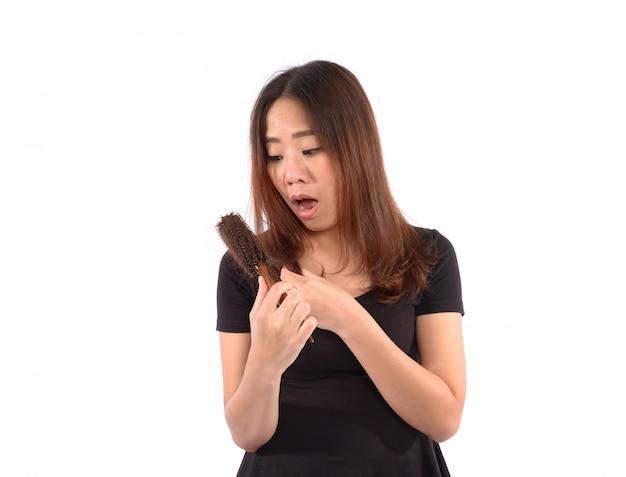 ショックを受けた女性の白で隔離されるヘアブラシで髪を失う