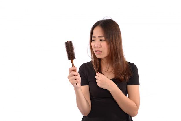 白で隔離されるヘアブラシで髪を失う女性