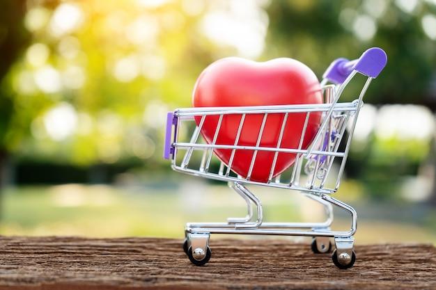 自然の背景の上のミニショッピングカートに赤いハート