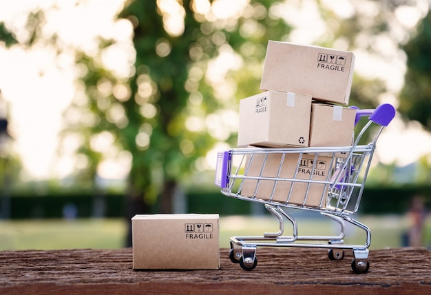 Бумажные коробки в тележке с копией пространства, покупки онлайн концепции