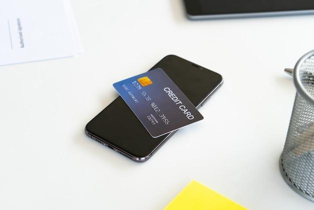 オフィスの机、オンラインショッピングの概念上のクレジットカードを持つスマートフォン