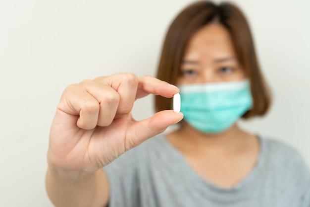 白い錠剤を持っている手でコロナウイルスを保護するためのマスクを着ている女性