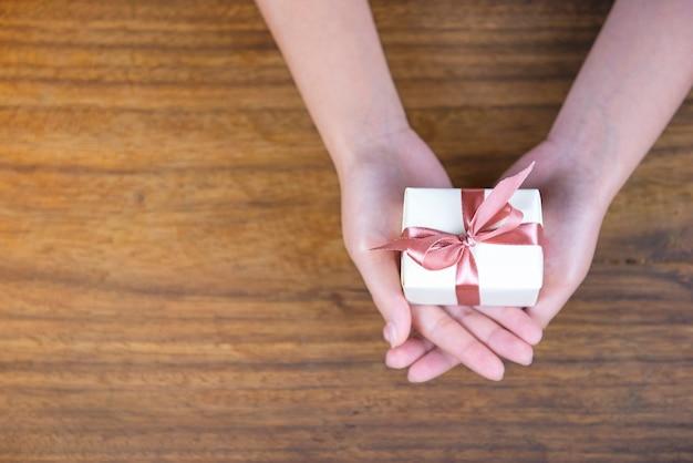 Подарите подарок на деревянном фоне, вид сверху