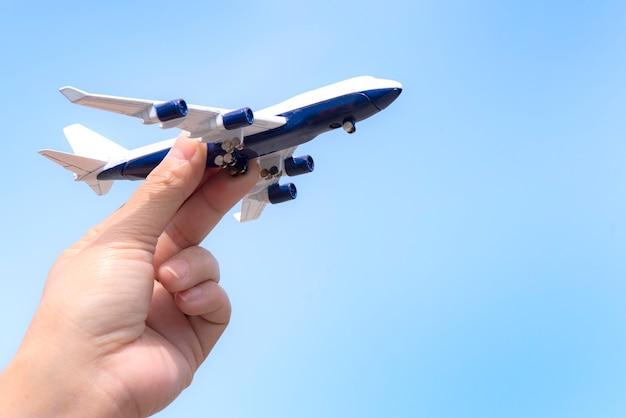 晴れた空に手に飛行機モデル。旅行、交通の概念