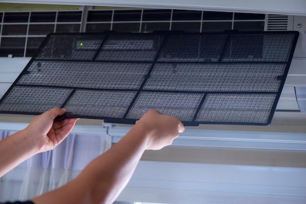 ほこりが多い室内でエアコンを掃除する男性技術者の手。エアコン内の基本洗浄剤