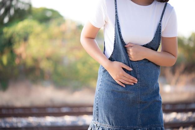 女性は痛みで彼女の胃を保持しています