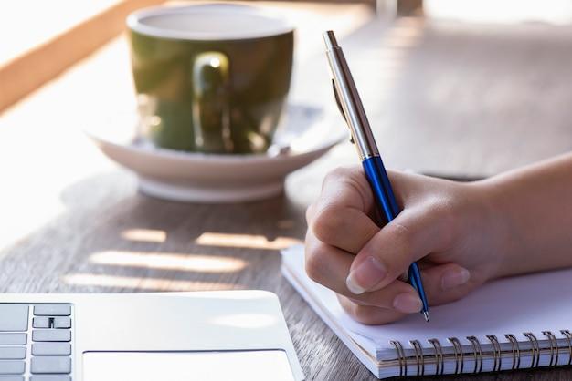 木の上に横に保持されているコーヒー・マグとノートの近くにペンを持つ手