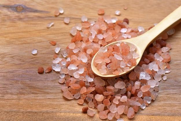 木材の背景に木のスプーンでヒマラヤの塩