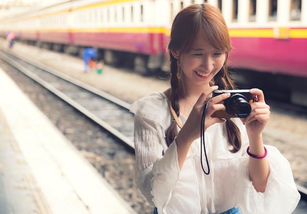 幸せな女性が駅でミラーレスカメラで写真を撮る
