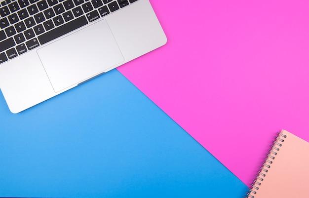 ピンクの背景の背景に置かれたラップトップおよびノートブック。パステル調の明るい色