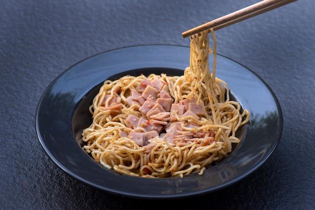 Спагетти с острой смешанной ветчиной на черной тарелке