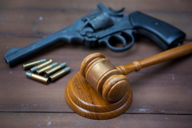 リボルバーとハンマーは木製のウェアの背景に落ち着き、合法的に武器を購入しました。犯罪、武器、法廷、法律