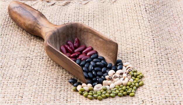 Различные виды зерновых бобов на деревянной ложкой