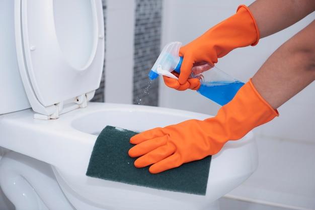 便器をスプレーで掃除し、汚れをこすります