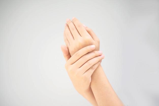 手をこするクリームを使用して若い女性