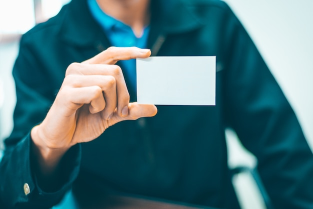 Деловой человек держит белую карточку