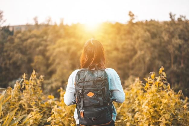 Молодая женщина с рюкзаком, стоя на берегу озера, концепция путешествия, свобода, образ жизни
