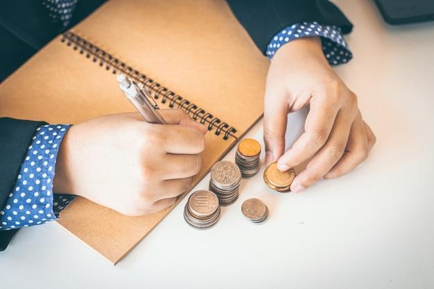 そろばんの計算を行うビジネス女性会計士の手。貯蓄、貯蓄融資のコンセプト。