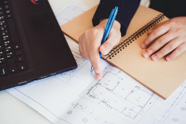 Профессиональный архитектор, глядя на планы строительства