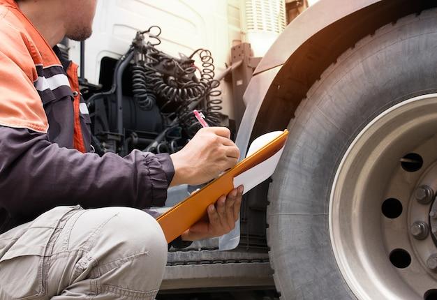 トラックドライバーは、トラックタイヤをチェックしてクリップボードを保持しています。
