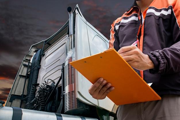 トラックの運転手はトラックを検査しながらクリップボードを保持しています。