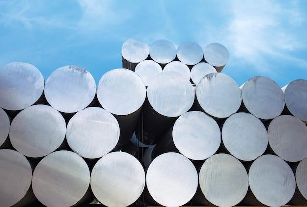 工業用原料、アルミプロファイル工場のアルミバーのヒープ。