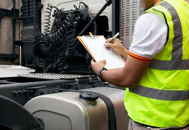 自動車整備士はトラックをチェックしながらクリップボードを保持しています。