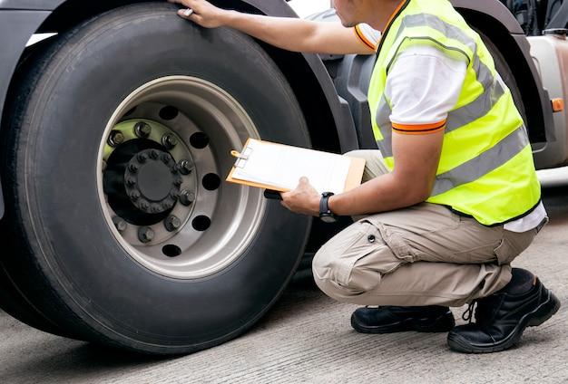 自動車整備士はトラックのタイヤをチェックしながらクリップボードを保持しています。