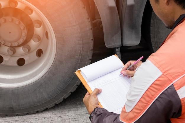 自動車整備士はトラックのタイヤを検査しながらクリップボードを持っています。