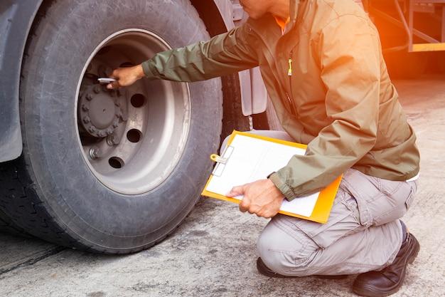 トラックの運転手はトラックのタイヤを検査しながらクリップボードを持っています。