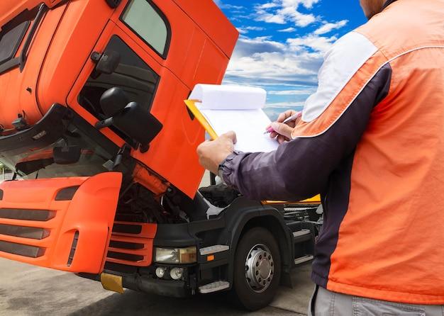 Водитель грузовика осматривает грузовик.