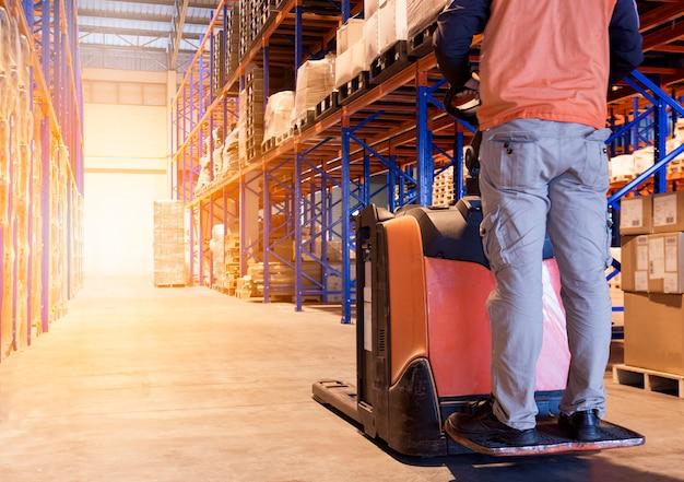 男性労働者は倉庫工場で電動フォークリフトを使用しています。