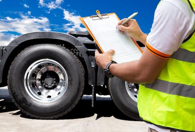 トラックの運転手はトラックのタイヤを検査しながらクリップボードに書き込みます。