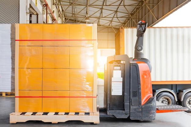 トラックへの商品パレットの積荷のある電気フォークリフトパレットジャッキ