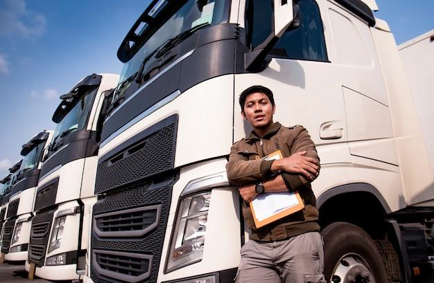現代の半トラックで立っているアジアのトラック運転手の肖像画