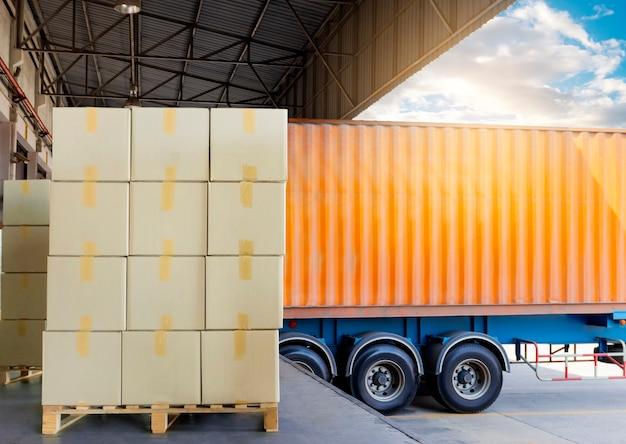 Стек картонных коробок при погрузке поддонов в грузовик