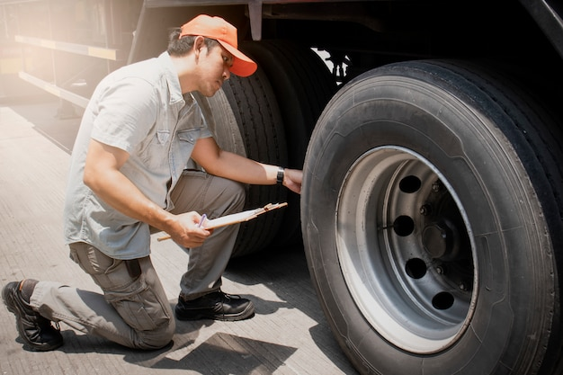 アジア人は安全を検査するクリップボードを保持しているトラックの運転手がトラックの車輪をチェックします。