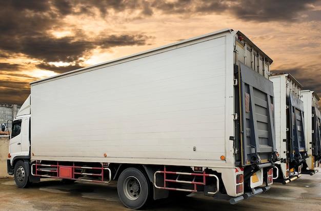 夕焼け空の駐車場のトラックコンテナー。道路貨物業界の配送物流と輸送。