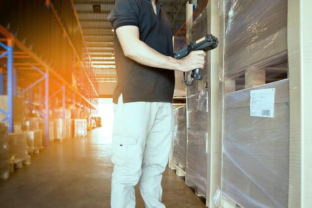 倉庫作業員は、製品パレットのチェックバーコードスキャナを保持しています。